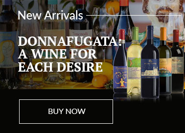 Five bottles of Donnafugata Wines from Sicily displayed in front of a colourful scene of wine bottles, ceramic heads, citrus fruits and fabrics.