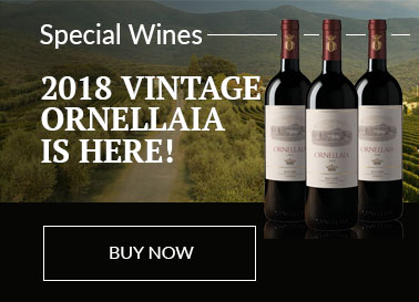 3 Bottles of Ornellaia 2018 Vintage sitting on a black base in front of a view of the Ornellaia vines at their vineyard.